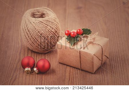 making christmas gits, a box with red holly berries, baubles and twine ribbon, toned poster