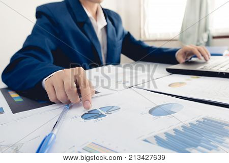 Business and finance investment concept : Businessman check about cost and doing finance graph report at office Finance managers taskBusinessman recheck new plan financial graph data.