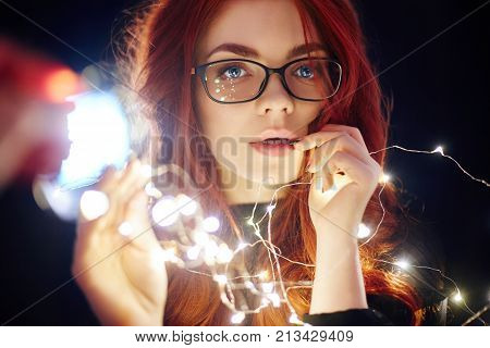 Art Portrait Of A Woman With Red Hair In Christmas Lights. Girl In Glasses With Reflected Christmas