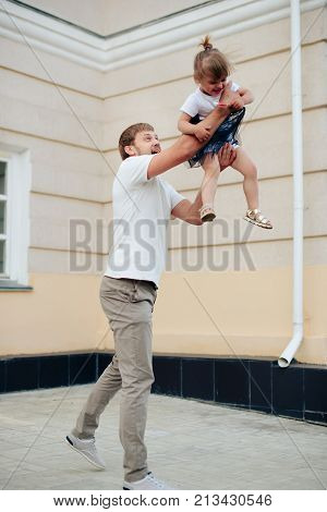 father holds little daughter in her arms on the background of the building 1