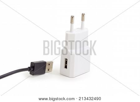 White AC adaptor for mobile phones battery charging with disconnected black cable compatible with USB on a light background
