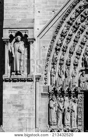 Architectural details of the facade of catholic cathedral Notre Dame de Paris in black and white. Notre-Dame cathedrall is built in French Gothic architecture. Paris France