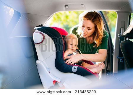 Young mother putting her little baby boy in the car seat, fastening seat belts.