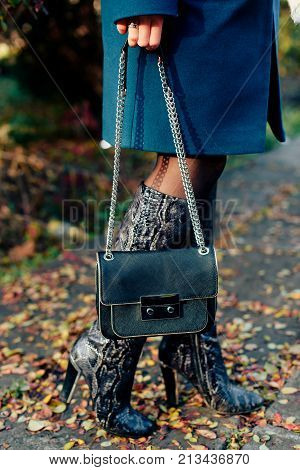 woman's legs in high boots with a lady's bag on a background of autumn leaves 1