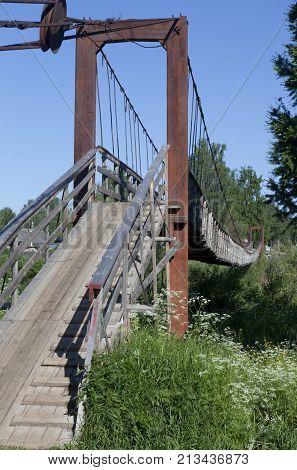 Suspension bridge over the river Vaga in the village Verkhovazhye of Vologda region, Russia