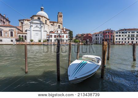 Chiesa di San Geremia and small white motorboat in the harbor in Venice Italy
