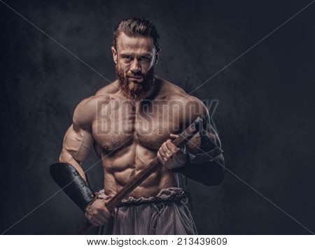 Artistic portrait of huge shirtless muscular Viking holds axe over dark grey background.