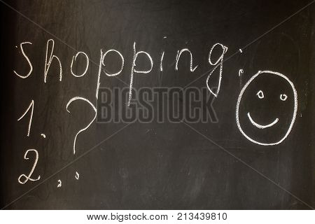 Inscription Shopping chalk on a black board with a question mark and a picture of a smiling face. Preparing for shopping shopping list good mood.