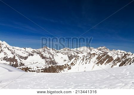 Wonderful landscape of sharply white snow in rocky mountains under blue sky.