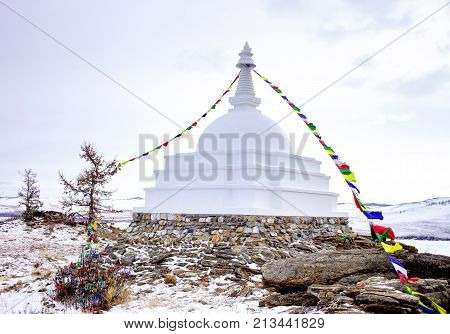 Buddhist stupa of enlightenment on the island Ogoy with flags. Baikal.