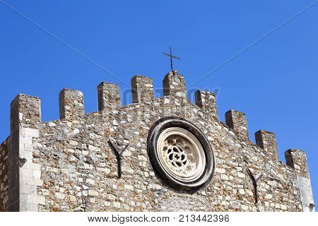 TAORMINA, ITALY. April 3, 2015: Detail of the crenellated wall roof of the church of St. Nicholas, Cathedral and Duomo from year 1980. Blue sky cloudless. Taormina, Sicily. Italy.