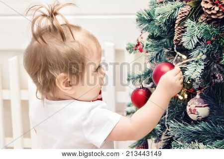 Cute little Girl  Baby rejoices Holiday New Year Christmas Xmas , decoration of fir tree. Expectation of gift, shot soft focus