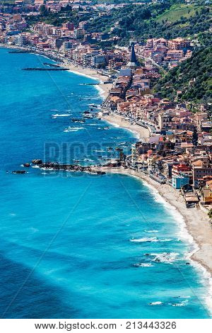 Aerial view of Sicily and the Mediterranean Sea. On the coast you can see the small town of Villa Gonia and Giardini Naxos. Place where the photo was taken: Taormina, Sicily (Italy)
