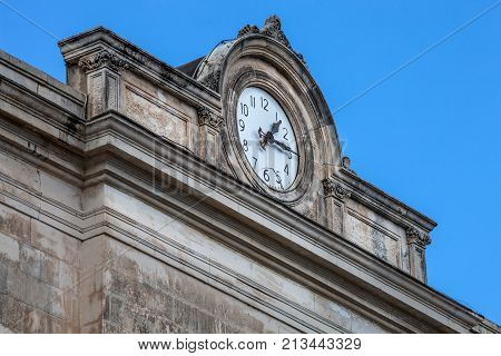 CATANIA, ITALY. April 3, 2015: Clock on the wall ledge roof of a historic building in Catania, Sicily in Italy. Blue sky without clouds.