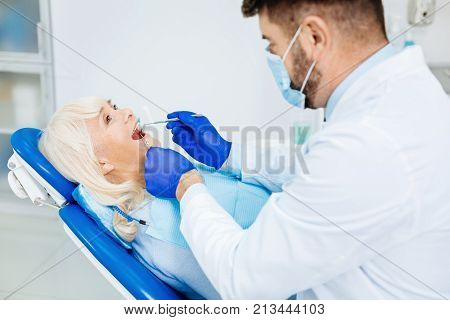 Experienced doctor. Close up of skilled dentist wearing mask and doing a mouth cavity checkup while using medical equipment