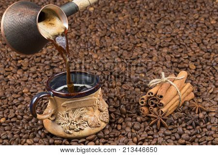 Hot aromatic coffee is poured from the pot into a clay cup. A cup with strong coffee on coffee beans. Coffee with foam cooked in a pot. Mug with coffee cinnamon and tubberry on coffee beans.