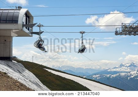 Rosa Khutor, Sochi, Russia - June 09, 2017: Funicular at the Rosa Khutor - Russian ski resort in Sochi. Tourists on a ski lift. Snowy caucasus mountains on background.