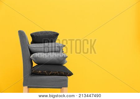 Chair with pillows on color background