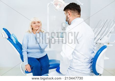 Feeling discomfort. Sad woman having medical consultation while sitting on the dental chair and touching her cheek