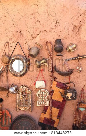 Traditional moroccan souvenirs - dagger, kettle, jug, window-mirror with shutters on clay wall, souk in Ait-Ben-Haddou Kasbah, Morocco, North Africa
