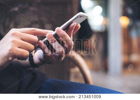 Closeup image of a woman's hands holding using and pointing at smart phone in modern cafe
