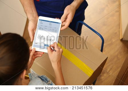 Woman appending signature after receiving parcel from courier at home