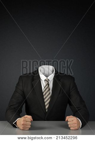 Businessman without head on dark background with copy-space