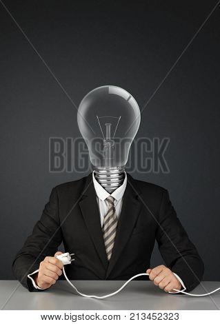 Businessman with light bulb head and plug switch ideas creative concept on black