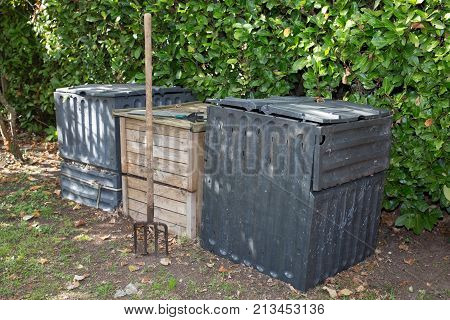 Garden Fork Turning Black Composted Soil In Wooden And Plastic Compost Bin