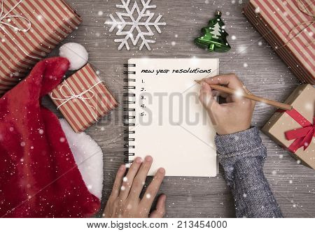 women hand write new year resolution on notebook. concept office christmas and happy new year.