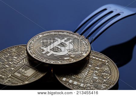 Fork of the crypto currency of bitcoin. A fork with gold bitcoins on a blue background. The concept of dividing the virtual currency bitcoin.
