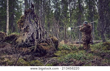 photographer works in thedeep forest, man in camouflage clothes