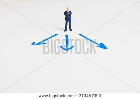 Miniature Businessman Standing On Arrow Pathway , Business Decision Concept.