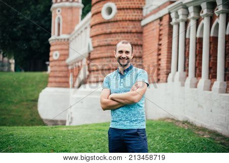 Man in a blue shirt with a beard in a park in nature, portrait