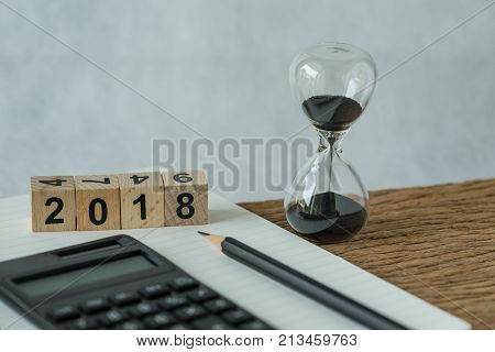 new year 2018 goals target or checklist concept as number 2018 wooden cube block with sandglass white paper note pencil and calculator on wooden table.