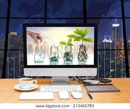 Workspace with computer desktop with Hand putting mix coins and seed in clear bottle at the screen on the trading graph over the blurred photo of cityscape background, 3D illustration