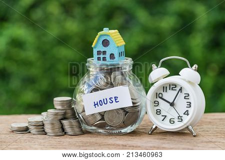 saving property or long term mortgage concept as glass jar with full of coins and miniature house label as House with white alarm clock.