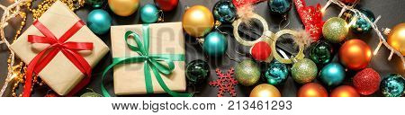 Christmas tree toys different colors balls gifts deer mask on a dark background Christmas New Year holidays preparation concept. Top view. Close-up.