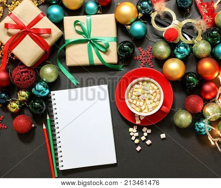 Christmas tree toys different colors balls gifts deer mask notebook pencils cup of coffee with marshmallows on a dark background Christmas New Year holidays preparation concept. Top view. Close.