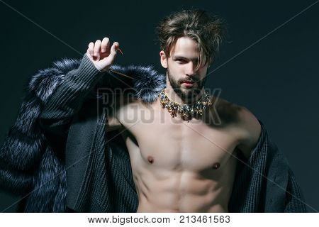 Man with fur coat on grey background. Cinderella prince with crown and muscular torso chest. Freak gay and transvestite. Drag queen homosexual and trans. Winter fashion jewelry accessory. poster