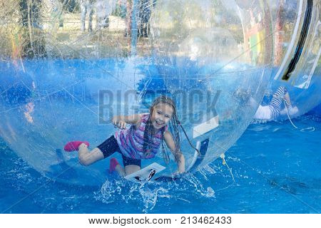 The joy of a child in motion and turning inside the zorb