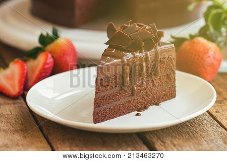 Triangle slices of delicious dark chocolate fudge cake decorated with chocolate curl on white plate put on wood table. Homemade bakery concept to present birthday cake party or cafe and restaurant. Chocolate fudge cake ready to served.