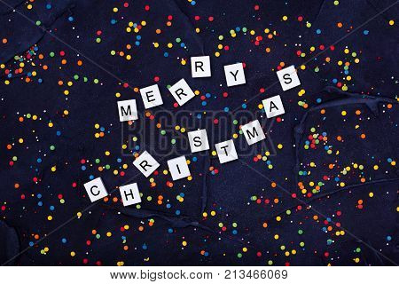 Flatlay of Colorful Round Candy Confetti and text Merry Christmas