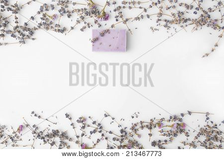 top view of handcrafted lavender soap with frame made of flowers on white surface poster