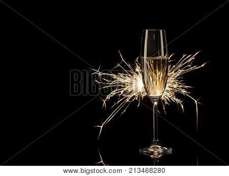 Tall glass of champagne in the glow of Bengal lights. Black background. Concept of celebration and New Year.