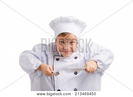 Little cook in uniform and white cap in anticipation of a delicious meal with cutlery on white isolated background