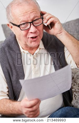 Senior citizen calling on the phone with his smartphone