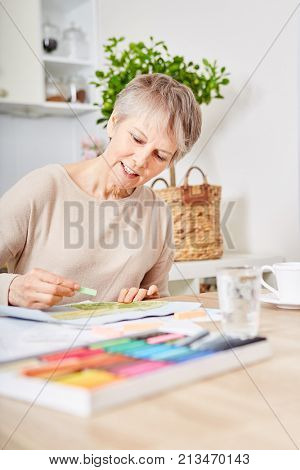 Senior woman with dementia creatinve painting with chalk as therapy