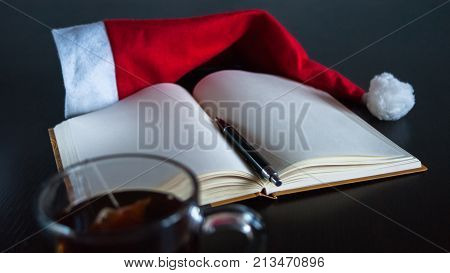 Planning Future On Christmas Concept: A Notebook With Blank Pages, A Black Pen, Santa Hat, Glass Mug