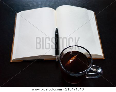 A Notebook With Blank Pages, A Black Pen, Glass Mug With Teabag On Dark Desk